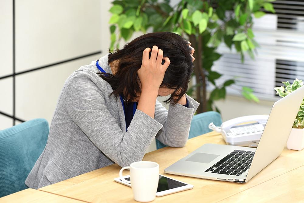 パソコンの前で悩む若い女性